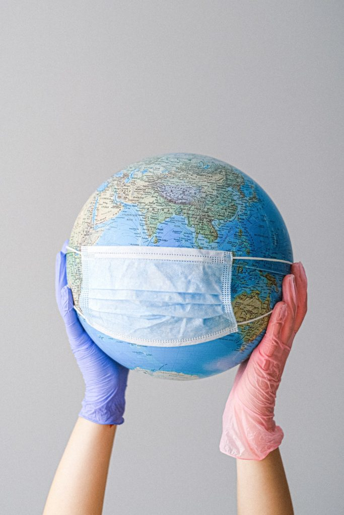 hands-with-latex-gloves-holding-a-globe-with-a-face-mask