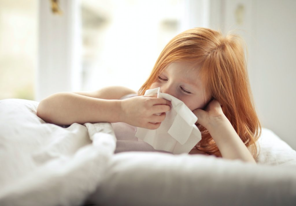 ill-preteen-girl-wiping-snot-while-resting-in-bed-at-home