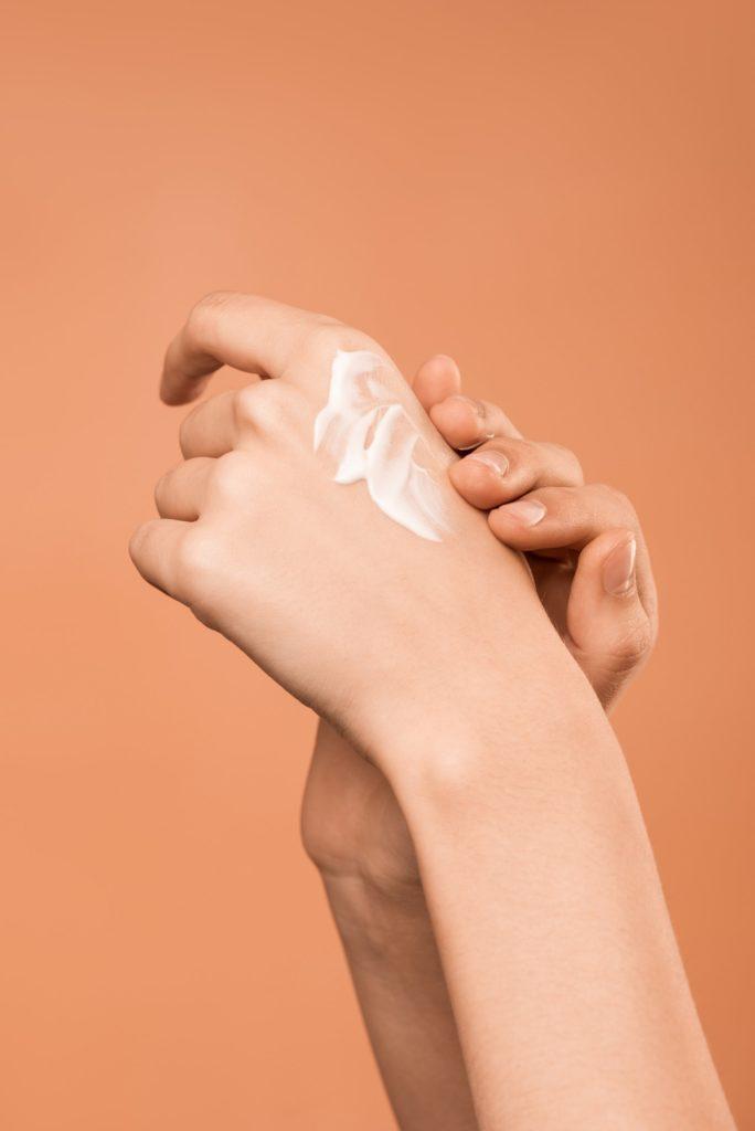 kak-spasti-kozhu-person-applying-hand-cream-israbell-com